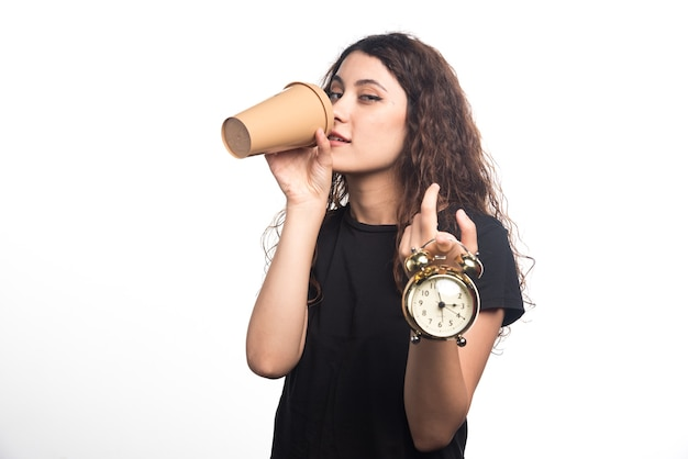 Young girl with clock in hand showing time and drinking coffee on white background. . high quality photo