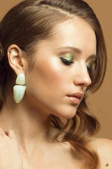 Молодая девушка с закрытыми глазами и красивым вечерним зеленым макияжем, вертикальное студийное фото.