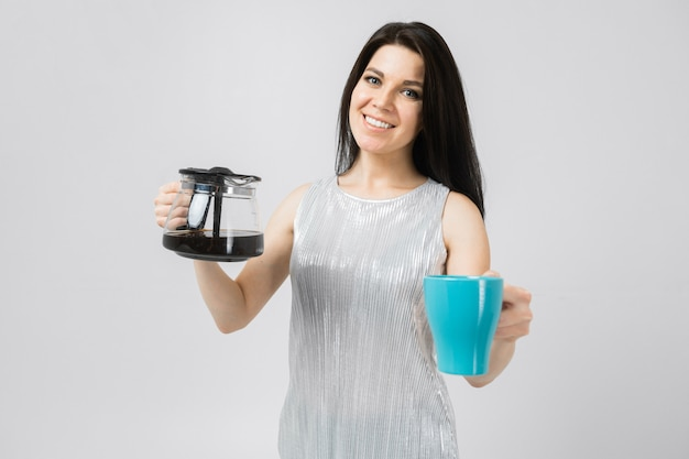 Young girl with a coffee pot and a mug stands isolated on light