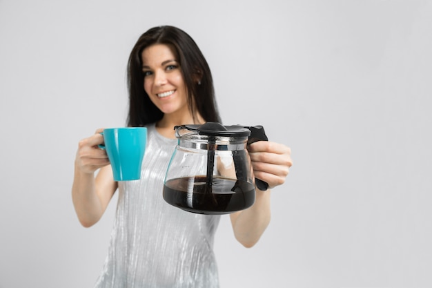 Young girl with a coffee pot and a mug stands isolated  a light