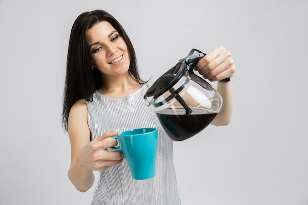 Young girl with a coffee pot and a mug stands on a light