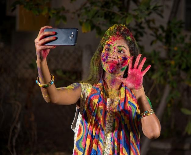 Молодая девушка с красочным лицом принимая selfie с помощью смартфонов на фестивале холи. концепция фестиваля и технологий