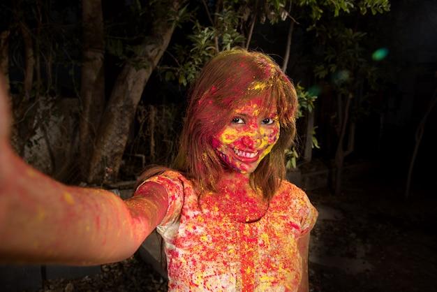 Holi 축제에 스마트 폰을 사용하여 셀카를 복용 화려한 얼굴을 가진 어린 소녀. 축제 및 기술 개념.