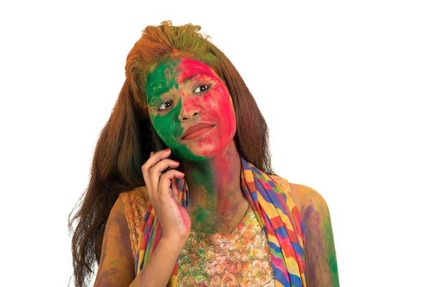 전화 통화 하 고 색상 holi의 축제를 축 하하는 화려한 얼굴을 가진 어린 소녀.