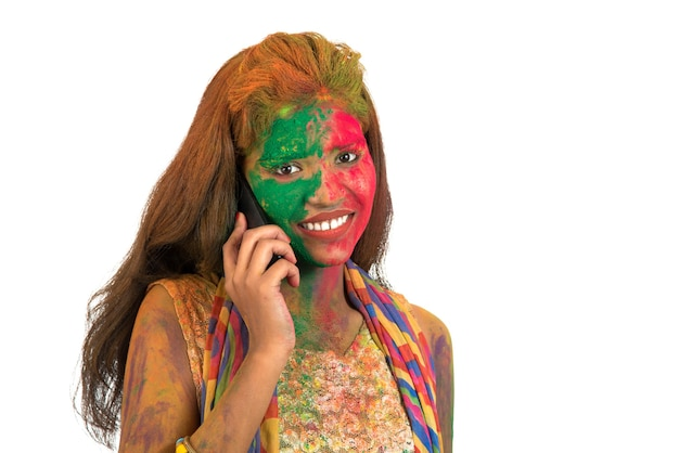 Young girl with colorful face talking on phone and celebrating festival of color holi.