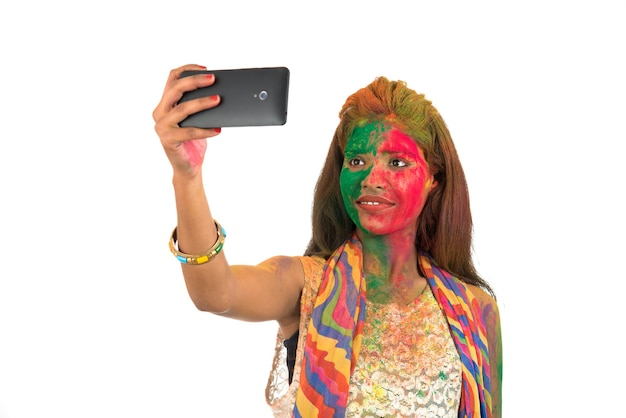 Holi 축제에 스마트 폰을 사용하여 셀카를 복용 화려한 얼굴을 가진 어린 소녀. 흰색 바탕에 축제 및 기술 개념입니다.