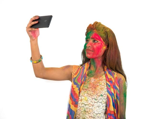 Holi 축제에 스마트 폰을 사용하여 셀카를 복용 화려한 얼굴을 가진 어린 소녀