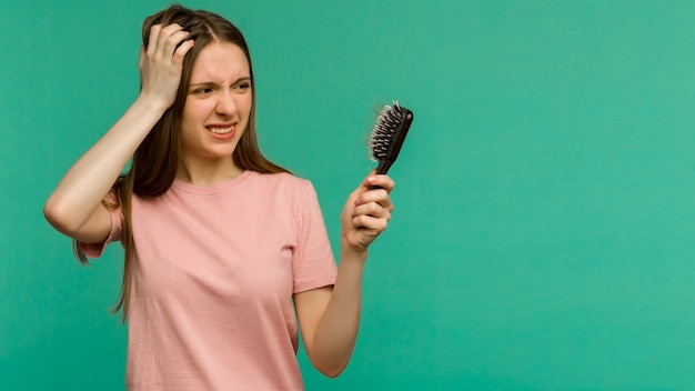 Young girl with a comb and problem hair on blue background - image