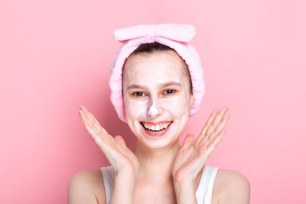 Молодая девушка с косметической маской на лице и широко улыбается