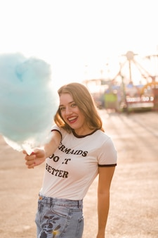 Young girl with cotton candy in the amusement park