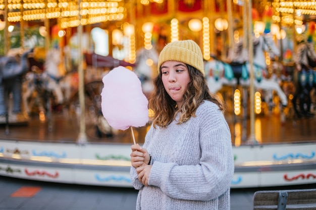 Young girl with a cotton candy at a christmas fair