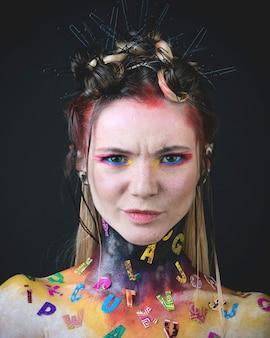 創造的なアルファベットの化粧を持つ若い女の子