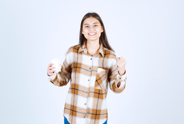 Молодая девушка с чашкой чая, чувствуя себя веселой на белой стене.