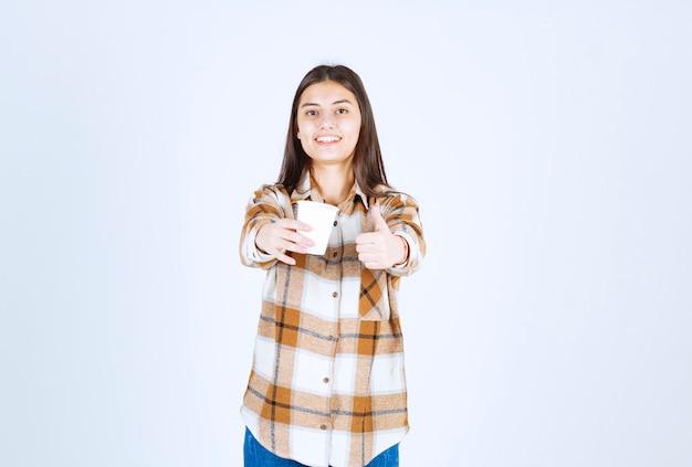 흰색 벽에 엄지손가락을 포기 하는 차 한잔과 함께 아름 다운 어린 소녀.