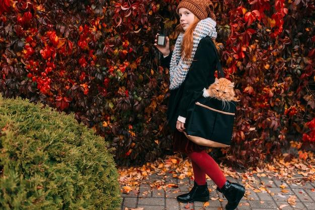 秋の公園で彼女のバッグの中の猫を運ぶ彼女の手でお茶のカップを持つ少女