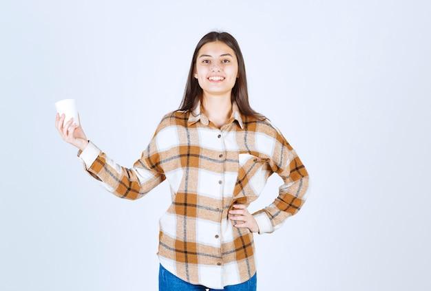 벽에 서 있는 차 한잔과 함께 아름 다운 어린 소녀.