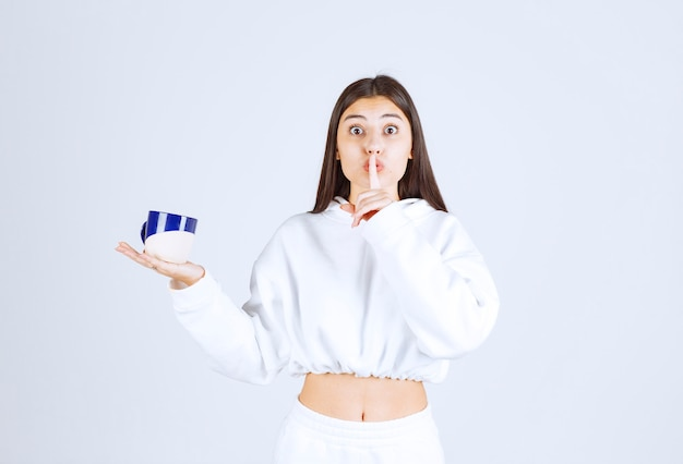 Giovane ragazza con una tazza che mostra segno silenzioso.