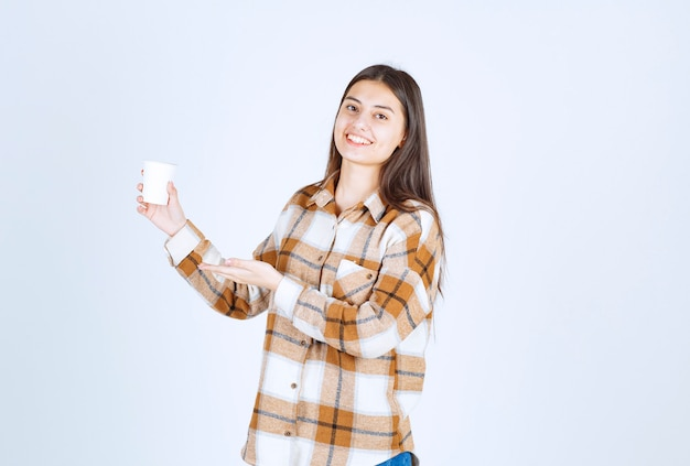 Young girl with cup of tea feeling happy on white wall.