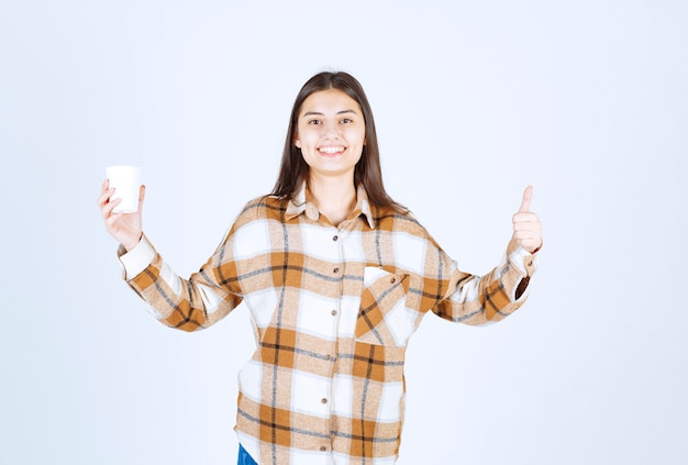 Young girl with cup of tea giving thumbs up on white wall.