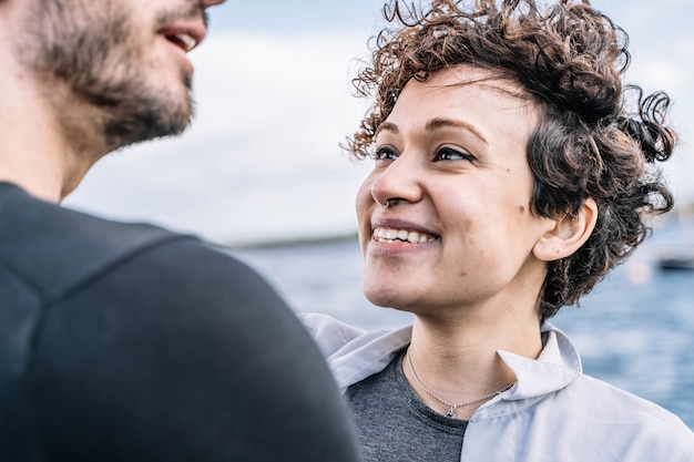 Young girl with curly hair and piercing  nose looking at his partner with the sea out of focus in the