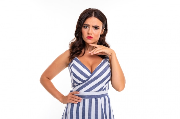 A young girl with a delightful smile, flat teeth, red lipstick, long wavy chestnut hair, beautiful makeup, in a white and blue dress in a stripe emotionally poses on camera