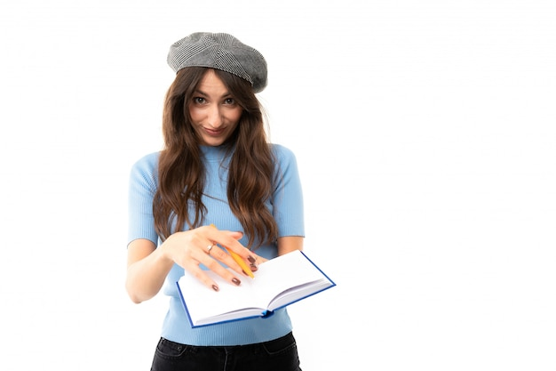 Young girl with delightful smile, long wavy chestnut hair, beautiful makeup, in blue jersey, black jeans, grey beret, standing with notebook and pen