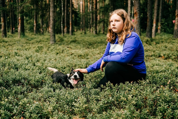 숲에서 포즈를 취하는 강아지와 어린 소녀