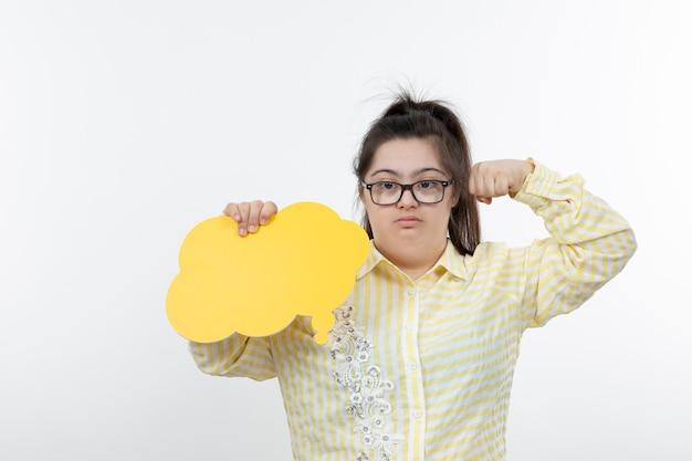 黄色の吹き出しを保持している眼鏡のダウン症の少女。