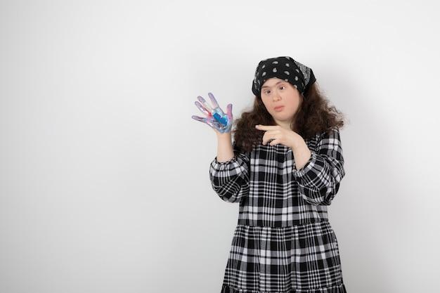 Молодая девушка с синдромом дауна показывает цвета на белом.