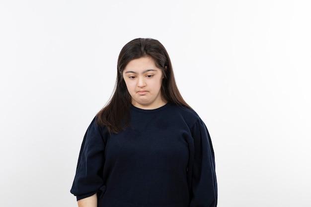 ダウン症の少女が立って悲しんでいます。