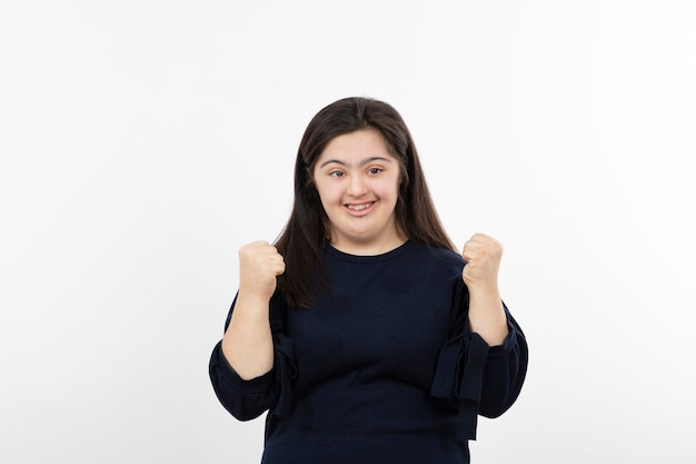 Молодая девушка с синдромом дауна стоя и позирует.