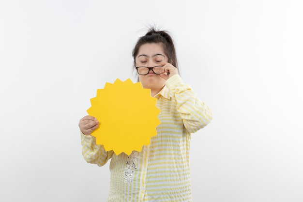Young girl with down syndrome with yellow speech bubble posing.