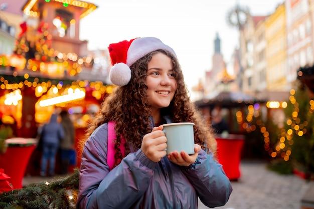 ポーランド、ヴロツワフのクリスマスマーケットでドリンクを飲みながら若い女の子