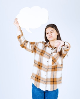 白い壁に親指を下に与える空のテキストの雲を持つ少女。