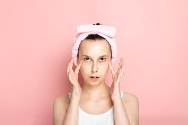 Молодая девушка с повязками на глаз смотрит вверх и касается руки лицом к лицу на розовом пространстве
