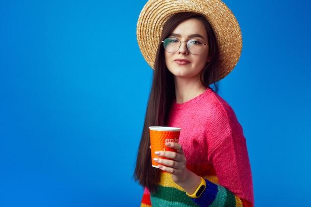 Молодая девушка в очках, держащая кофе на вынос, имеет радостное выражение