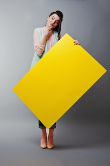 Young girl with face hold yellow blank paper. young  woman show blank card. girl with long hair portrait isolated on gray background.