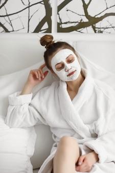 フェイスマスクを持つ少女。スキンケア。白い背景の上に顔のマスクでリラックスした美しい少女