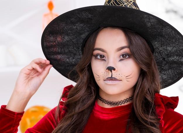 Молодая девушка с лицом окрашены для хэллоуина крупным планом