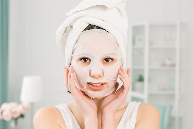 光空間でカメラを見て顔のマスクを持つ少女。化粧品の手順。美容スパと美容。