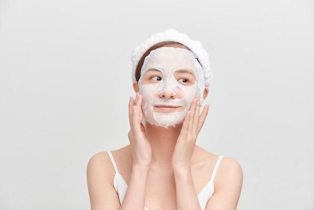 白い背景の上のカメラを見ている顔のマスクを持つ少女。美容処置。ビューティースパと美容。