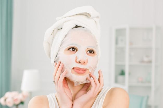 顔のマスクを持つ少女は、明るい空間を見つめています。化粧品の手順。美容スパと美容。