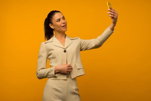 Молодая девушка с проблемами кожи лица позирует со смартфоном на желтом фоне.