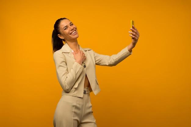 黄色の背景にスマートフォンでポーズをとって顔の皮膚の問題を持つ少女。