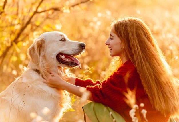 秋の自然の真ん中でゴールデンレトリバー犬をかわいがって野の花を持つ少女