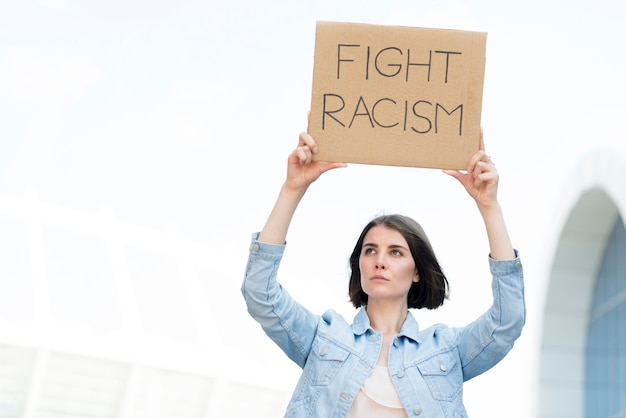 Young girl with fight racism quote on cardboard