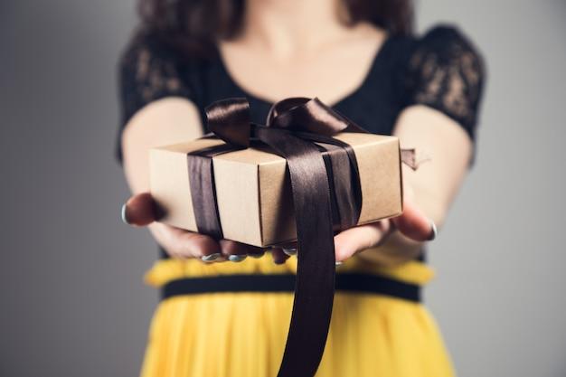 회색 배경에 선물 상자가 있는 어린 소녀