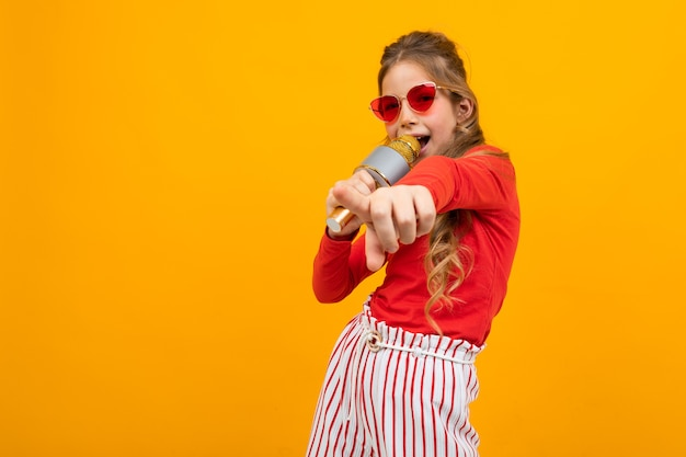 Young girl with glasses comes off for music with a microphone in her hands on a yellow studio background with copy space.