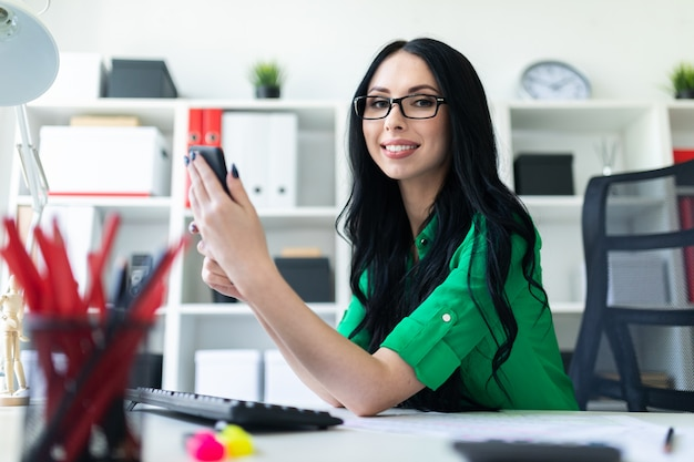Young girl with glasses at the office looks holding in phone hands and smiling.