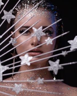Молодая девушка с блестящим макияжем и украшением в виде короны со звездами на темном фоне.